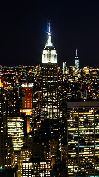 Photograph of the Empire State building lit up at night, surrounded by other buildings.