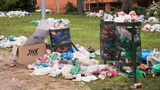 Plastic bags, bottles, boxes and cans overflowing from bins and on floor.