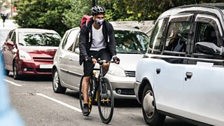 Commuter on bike wearing pollution mask