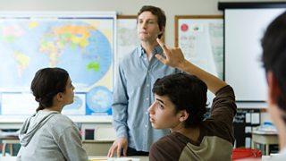 Boy raises hand in class