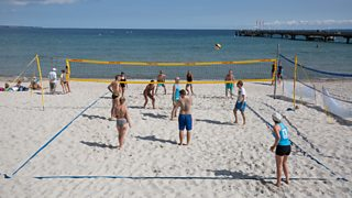 People playing volleyball on a beach