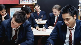 Teenagers writing at desks in classroom