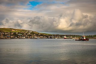 A small boat leaving the Port of Stromness, Mainland Orkney, Scotland, UK