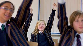 Students wearing school uniform raise their hands in classroom