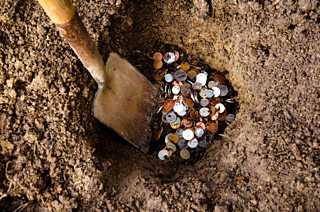 A photo of money in a hole in the ground