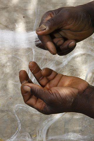 Photo of hands knotting a fishing net on Lagdo Lake