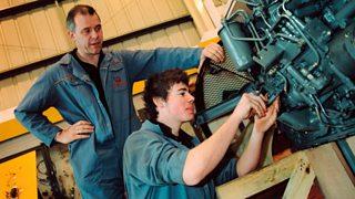 Apprentice using machine in workshop