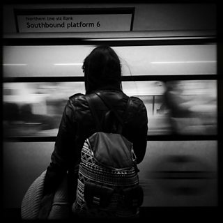 A black and white photo of girl on train platform