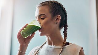 Young woman drinks a smoothie in kitchen