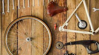 A disassembled bike with its parts neatly laid out on a wooden table.