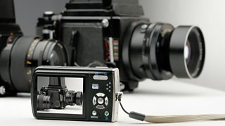 A photograph of a large camera is displayed on the screen of a small digital camera.