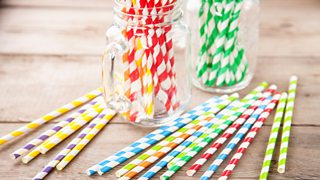 A collection of colourful paper straws displayed in two clear jars and on a wooden table.