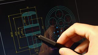 A designer working on a CAD blueprint is using his pen to point at the design.