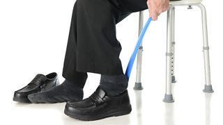 An elderly man sliding into his shoes with the aid of a long-handled shoehorn.