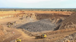 A large open pit for manganese mining with yellow trucks and diggers.
