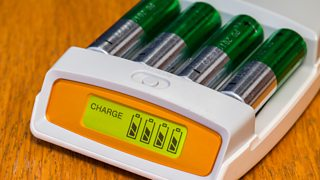 A set of four AA rechargeable batteries on charge.