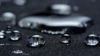 A close-up image of water droplets on a dark waterproof fabric.