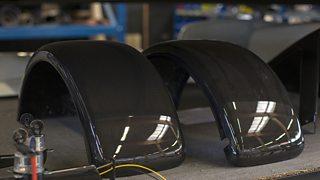 Carbon-reinforced plastic (CRP) mudguard parts for automobiles sit on a table.