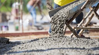 A close-up image of concrete being poured to construct floors of a building.