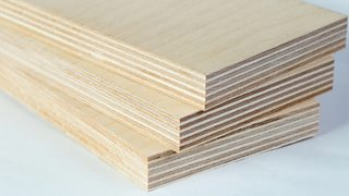 A stack of three pieces of light plywood boards.