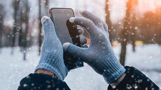 A man using a smartphone in the snow with gloves adapted to be able to use touch screens.