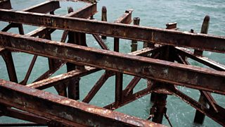 Rusted metal framework at a pier overhanging the blue sea.