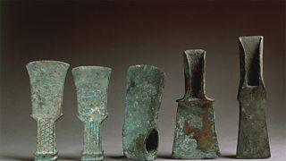 A historic collection of axes showing copper oxidising to a green colour (verdigris).