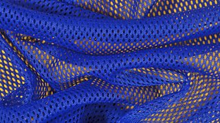 A close-up image of bright blue, crumpled, non-woven, bonded fabric on a yellow background.
