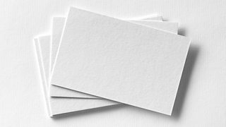 A stack of mock-up business cards on white textured paper.