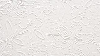 A close-up segment of an embossed floral pattern on white paper.