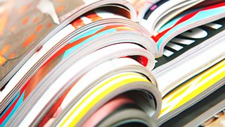 A close-up image of the center binders of a stack of colourful printed magazines.