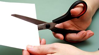 A pair of hands shown holding a piece of white card and a pair of scissors cutting it.