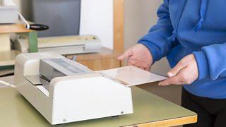 A woman's hands feeding a document through a laminating machine.
