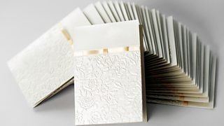 A stack of hand-made, embossed wedding cards in ivory with a gold ribbon detail.