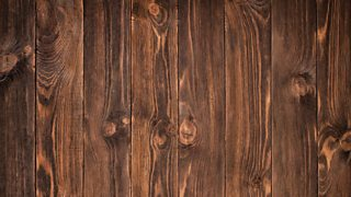 A close-up image of dark-stained, distressed timber flooring in a walnut shade.