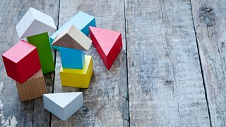A collection of colourful, small children's wooden building blocks placed on a wooden floor.
