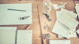 Flat-pack, chipboard furniture parts with instructions and tools.