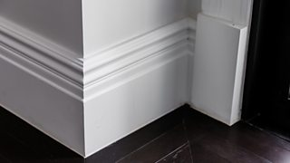 A close-up image of a white luxury skirting board against a dark wooden floor.