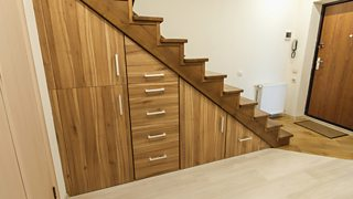 A modern, wooden, built-in storage space with cupboards and drawers underneath a staircase.