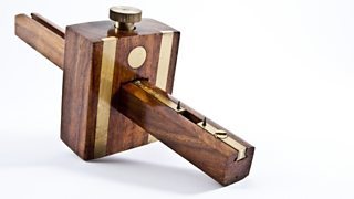 A dark wooden mortise gauge with a rectangular design in the centre.