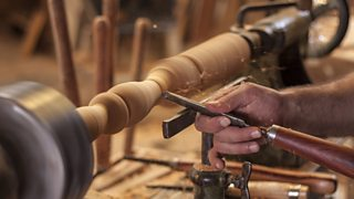A worker's hands shown turning wood to shape it with a tool on a spindle lathe.