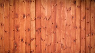 A close-up of the grain texture of brown, varnished wooden flooring.