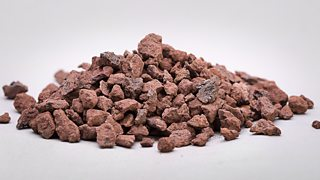 A heap of small clusters of natural iron ore in a red shade, isolated on a white background.