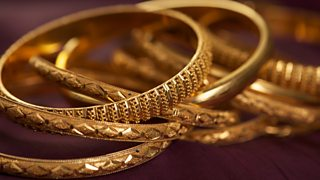 A detailed close-up image of a collection of intricate gold bangles.
