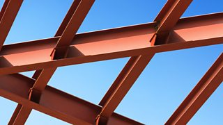 A large construction of red steel beams against the bright blue sky.