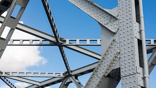 A large, grey, detailed construction showing metal bracing against the blue sky.