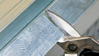 A close-up image of tin snips cutting a piece of steel.