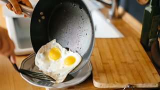 Some hands moving two fried eggs with a spatula from a black non-stick pan to a plate.