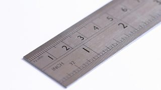 A close-up of a metal ruler showing up to three inches, isolated on a white backdrop.