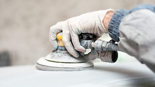 A gloved hand using a buffing machine to polish a car for painting.